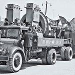 Экземпляр МАЗ-200П, № 12-98 мдг, буксирующий прицеп Т-151А на праздничной демонстрации в г. Тирасполе. Украшенный транспарантами и флагами автопоезд демонстрирует продукцию производственно-технического объединения «Электромаш». Молдавская ССР, 1 мая 1964 г.