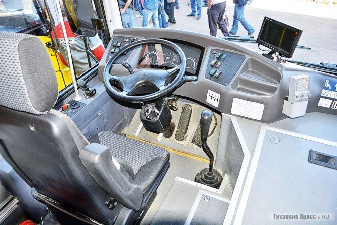 Интерьер кабины «школьника» отличается от обычного автобуса лишь вспомогательным оборудованием: монитор на панели передает изображение с камеры, а коробка справа – пульт системы пожаротушения
