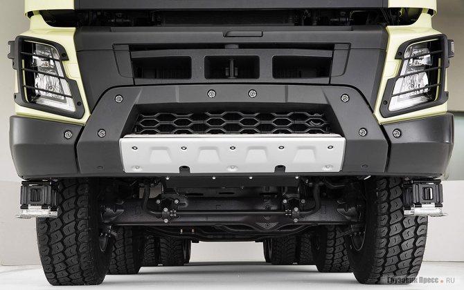 Компоновка бампера и переднего пространства FMX продумана великолепно: высокий клиренс, короткий свес, защищённый и быстро сменяемый бампер. Над бампером видна буксирная проушина из литейного чугуна с нагрузкой до 32 т